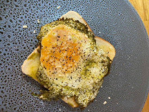 Image of Mels take on the TikTok trend pesto fried eggs. A square piece of buttered toast with a fried egg + pesto on top. The toast sits on a black speckled plate
