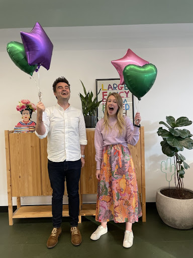 Image of our two new staff members Hugh and Georgia holding two helium balloons each. Hugh wears a white, button down shirt with black pants and tan lace up shoes. Georgia wears a purple jumper tucked into a multicoloured maxi skirt and white sneakers