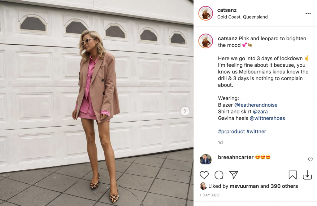 Image of a screenshot taken from an Instagram feed of influencer Cat Sanz. Cat is standing on an angle, looking to the left and is wearing a pink skirt suit, beige blazer and leopard print heels. She has her hands by her side and is looking off to the left with sunglasses on.